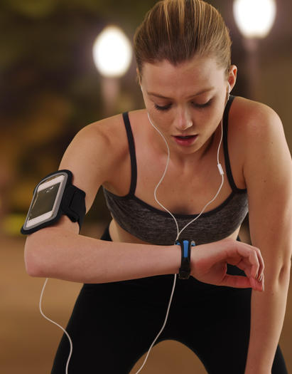Woman in performance activewear checks her heart rate while jogging to show how technology enhances clothing and life.